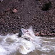 A raft crashing through the largest wave in Hermit Rapid.