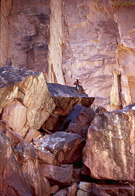 Thumbnail image ofA commercial river guide dwarfed by rocks and...