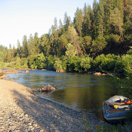 A private boat tied up at camp on the South Fork of the American River, with the shadow of the photographer.