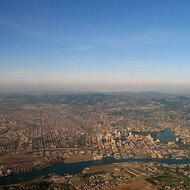An aerial view of Alameda (foreground), Oakland (including Lake Merritt), and Berkeley (background).