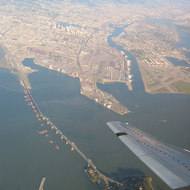 An aerial view of a portion of the San Francisco Bay Bridge (foreground) Alameda (right), and Oakland (left, including Lake Merritt).