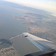 An aerial view of a portion of the San Francisco Bay Bridge, Treasure Island (foreground), and San Francisco (right).
