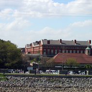 A view of Jackson Square from the Mississippi River, focusing on the Pontalba building and Cafe du Monde (foreground).