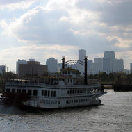 A Mississippi River steamboat with the New Orleans skyline in the background.