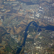 An aerial view of Redding, CA with the Sundial Bridge in the center across the Sacramento River.