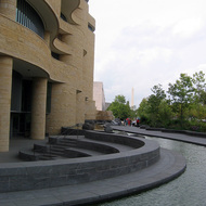 The exterior of the Museum of the American Indian with the Washington Monument in the background, Washington, DC.