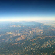 An aerial view of the Sierra Nevada Mountains with Lake Tahoe in the background.