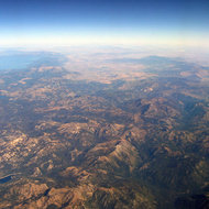 An aerial view of the Sierra Nevada Mountains with Lake Tahoe and Reno, Nevada in the background.