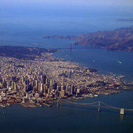 An aerial view of San Francisco, CA, including the Golden Gate Bridge and part of the Bay Bridge.