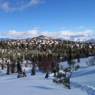 A view from Tahoe-Donner Cross-Country east to Sierra Nevada peaks north of Lake Tahoe, with skiers.