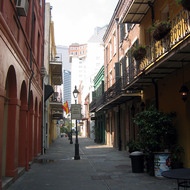 A French Quarter alley, looking toward the downtown high-rise buildings.
