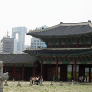 A view of the entrance to the Gyeongbokgung Palace grounds, looking back toward the modern downtown, including the dramatic and distinctive Jongno Tower.