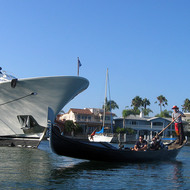 A gondola among the canals of Coronado Island, passing a yacht.