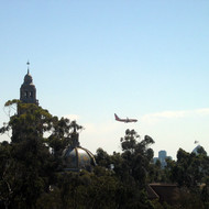 A view from the aerial tram at the San Diego Zoo, looking past the San Diego Musuem of Man to a jet landing.