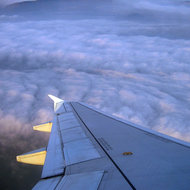 A view of clouds from a banking commercial jet.