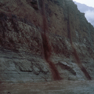 A rainstorm causes flash floods that spill over the cliffs above the Colorado River in the Grand Canyon.
