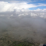 An aerial view of San Francisco, covered in clouds, with the San Francisco Golf Club below.
