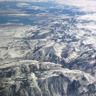 An aerial view of the crest of the Sierra Nevada Mountains, with Mono Lake in the upper left.