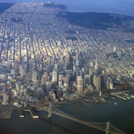 An aerial view of downtown San Francisco and a portion of the Bay Bridge, with Golden Gate Park (upper left) and the Presidio (upper right with the southern tip of the Golden Gate Bridge) in the distance.