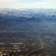An aerial view of Salt Lake International Airport (lower left), Salt Lake City (middle) and the mountain ranges beyond.