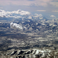 An aerial view across the Wasatch Mountains, looking toward Mount Timpanagos in the distance.