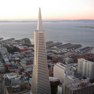 A view of the Transamerica pyramid and San Francisco Bay piers from the top of the Bank of America building at dusk.