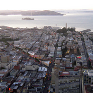 A view of San Francisco, including Coit Tower and Alcatraz Island, from the top of the Bank of America building at dusk.