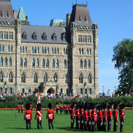 The changing of the guard at the Canadian Parliament, with part of the Centre Block in the background.
