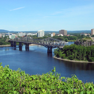 Pont Alexandra Bridge and Nepean Point as seen from Parliament Hill, with Gatineau, Quábec in the background.
