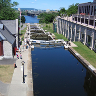 The Rideau Canal locks, leading to the Ottawa River. The Fairmont Chateau Laurier is on the right, and the Canadian Parliament complex is on the left. The Pont Alexandra Bridge leading to Gatineau, QC is in the distant background.