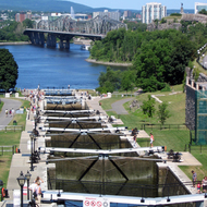 The Rideau Canal locks, leading to the Ottawa River. The Fairmont Chateau Laurier is on the right, and the Canadian Parliament complex is on the left. The Pont Alexandra Bridge leading to Gatineau, QC is in the background.