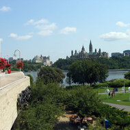 The grounds of the Canadian Museum of Civilization (foreground, in Hull, Quebec) with the Fairmont Chauteau Laurier (left) and the Canadian Parliament (right) in the background, across the Ottawa River in Ottawa.