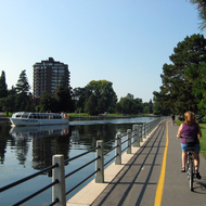 A tour boat on the Rideau Canal and bicyclists (the picture was taken from a bike) on the bike path alongside.