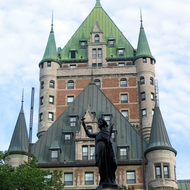 A statue of Maisonneuve at the Place d'Armes in Quebec with the Fairmont le Chateau Frontenac behind.