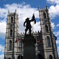 A view of the Notre-Dame Basilica from the Place d'Armes in Montreal behind a statue of Paul Chomedey de Maisonneuve.