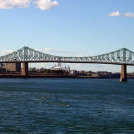 The Pont Jacques Cartier Bridge across part of the St. Lawrence River with the Biodome and Olympic Tower in the background.