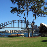 A view of the Sydney Harbour Bridge, a ferry, and the Sydney Opera House from the Government House lawn.
