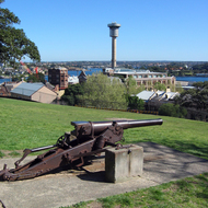 An old gun and the Harbour Control Tower from Observatory Hill, Sydney.