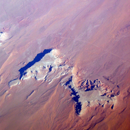 An aerial view of a butte and eroded land in the Western United States.