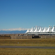 The Denver International Airport and the snowy peaks of the Rocky Mountains beyond that the airport design is meant to evoke.