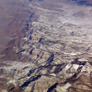 An aerial view of a mountain range in the west in winter.