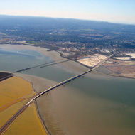 An aerial view of Dunbarton Bridge, the San Francisco Bay wetlands, and salt ponds.