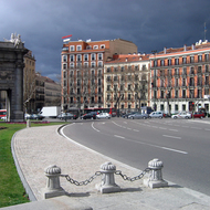 The Puerta de Alcalá on the left with nearby buildings and a building storm.