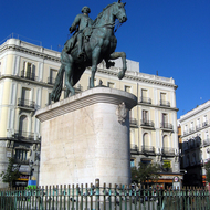 A monument to King Charles III at the Puerta del Sol.