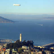 An airship passing over Coit Tower in San Francisco, taken from the top of the Bank of America building.