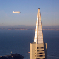 An airship passing behind the Transamerica Pyramid in San Francisco, taken from the top of the Bank of America building.