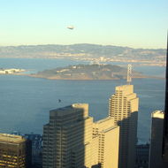 An airship behind the Embarcadero Center towers with Yerba Buena Island in the middle distance and the East Bay beyond, from the Bank of America building.