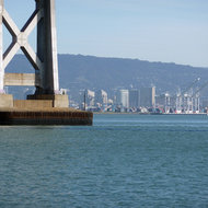 A piling of the San Francisco Bay Bridge, with the port and downtown area of Oakland in the background.