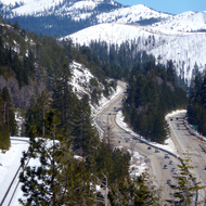 Interstate 80 and a train track going over the Sierra Nevada Mountains in winter.