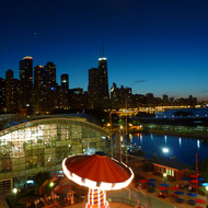 An amusement ride and the Chicago skyline at night from the Ferris Wheel at Navy Pier.